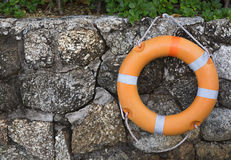 Lifebuoy hanging on a stone wall. Orange lifebuoy hanging on a stone wall Royalty Free Stock Photography