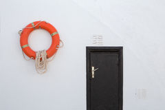 Lifebuoy, hanging on a white wall. Orange lifebuoy hanging on a white wall and thus forms a color contrast Royalty Free Stock Images
