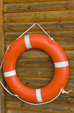 Lifebuoy hanging on a wooden wall. A bright orange lifebuoy hanging on a wooden wall at a swimming pool Stock Photography