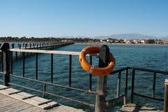 Lifebuoy i molo Pomarańczowy lifebuoy na bariera filarze Save lifebuoy i błękitne wody Zbawczy wyposażenie na doku dla nagłego wy Zdjęcia Stock