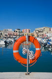 Lifebuoy. Image of a lifebuoy with seaport in background Royalty Free Stock Photo