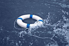 Lifebuoy, lifebelt, lifesaver in ocean storm as help, hope conce Royalty Free Stock Images