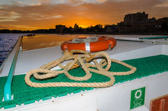 Lifebuoy with line and rope. On the ship at sunset and clouds Royalty Free Stock Image