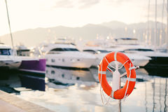 Lifebuoy in the marina for yachts. Red circle on the boat dock. Royalty Free Stock Photography