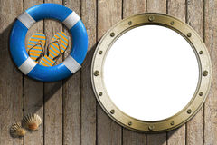 Lifebuoy and Metal Porthole on wooden wall Royalty Free Stock Image