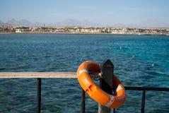 Lifebuoy na barierze Pomarańczowy Lifebuoy i błękitne wody Zamyka up Lifebuoy na filarze obraz royalty free