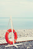 Lifebuoy next to wooden path on the beach Royalty Free Stock Image