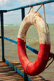 Lifebuoy. Old red and white rope tied to the dock by the sea, the sun shines and clouds Royalty Free Stock Images