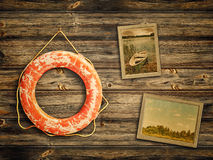 Lifebuoy and old travel photos. At wooden background Stock Photography