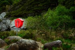 Lifebuoy. Orange lifebuoy stand mounted on a rock at lake shore Stock Image