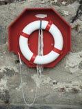 Lifebuoy ordnete auf der alten Wand an Stockbilder