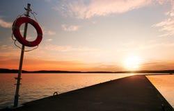 Lifebuoy på pir i den orange soluppgången Royaltyfri Foto