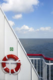 Lifebuoy and part of ship at sea with blue sky and clouds Royalty Free Stock Images