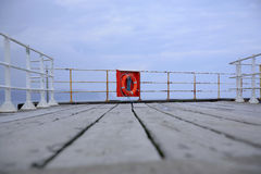 Lifebuoy on pier. With sea and cloudscape background Royalty Free Stock Images