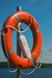 Lifebuoy on a pole. Red lifebuoy on the pier on the background of blue sky and lake Stock Image
