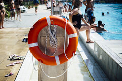 Lifebuoy on post in public swimming pool in summer Stock Image