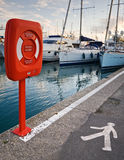 Lifebuoy in the red container. Placed on the edge of yacht pier Stock Photos