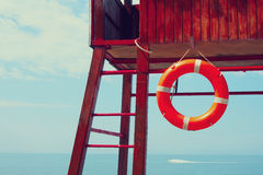 Lifebuoy on a rescue tower near the sea Stock Photos