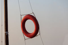 Lifebuoy. For rescuers. Red. Horizontal photo. The circle hangs on the ropes. Royalty Free Stock Photography