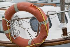 A lifebuoy or ring buoy preserver on the boat. A lifebuoy, ring buoy, lifering, lifesaver, life donut, life preserver on the boat. Lifebuoy tied to the small royalty free stock photography
