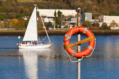 A lifebuoy. With a river and a boat in the background Stock Image