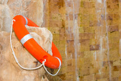 Lifebuoy is on the rock near the waterfall Royalty Free Stock Photography