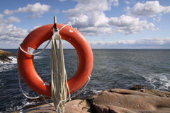 Lifebuoy on the rocks. A red orange lifebuoy standing in full sun in front of a turblent water front. Backgroung horizon showing water line and a blue sky with Royalty Free Stock Photography