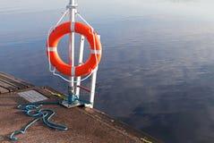 Lifebuoy rojo brillante en el embarcadero Imagenes de archivo