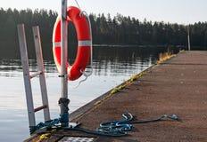Lifebuoy rojo brillante en el embarcadero Foto de archivo libre de regalías