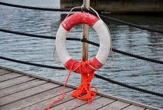 Lifebuoy rojo delante del mar azul Foto de archivo