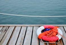 Lifebuoy rojo delante del mar azul Fotos de archivo