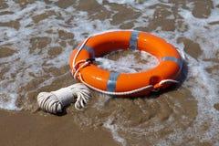 Lifebuoy rojo en ondas espumosas Foto de archivo libre de regalías