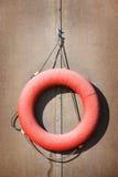 Lifebuoy rojo viejo en la pared Foto de archivo libre de regalías