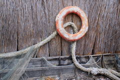 Lifebuoy. And rope hanging on a wall of reeds and an old wooden boat Stock Image