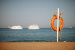 Lifebuoy and rope on the sea shore Stock Photos