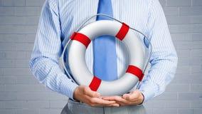 Lifebuoy rouge avec l'être humain d'isolement sur le fond blanc Photo libre de droits