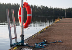 Lifebuoy rouge lumineux sur le pilier Photo libre de droits
