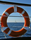 Lifebuoy and sailing boat Royalty Free Stock Image
