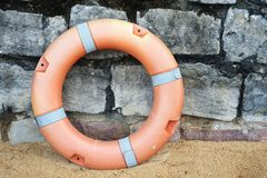 Lifebuoy on the sand and stone Stock Photography