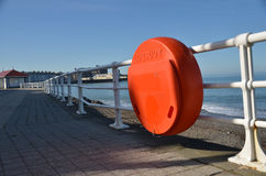 Lifebuoy at seaside. Lifebuoys hang on railings along walkway at seafront location Royalty Free Stock Images