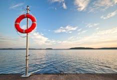 Lifebuoy seguro rojo brillante en el embarcadero Foto de archivo