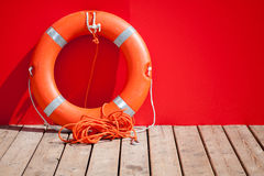 Lifebuoy stands on wooden floor Stock Image