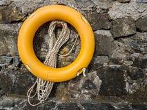 Lifebuoy on stonewall. Lifebuoy and rope hanging on stonewall Royalty Free Stock Photo