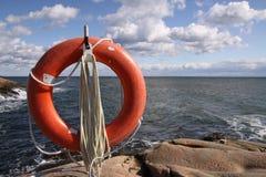 Lifebuoy sur les roches Photographie stock libre de droits