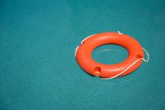 Lifebuoy in swimming pool. Orange lifebuoy on blue swimming pool water surface stock photography