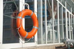 Lifebuoy in the swimming pool. Orange lifebuoy on a wall of a protection of the swimming pool Stock Images