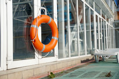 Lifebuoy in the swimming pool. Orange lifebuoy on a wall of a protection of the swimming pool Stock Photo