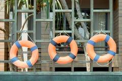 Lifebuoy. Three lifebuoys are hanging on wood frame royalty free stock photography