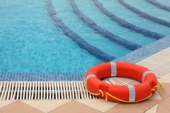 Lifebuoy on tiled floor near swimming pool stock photos