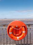 Lifebuoy and views out to sea. Bright orange lifebuoy against railings overlooking the sea at low tide out to island of Steep Holm in Somerset.  Blue sky and Stock Photos